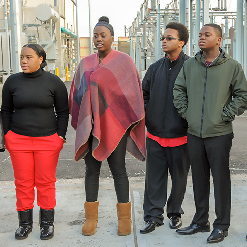Four singers at a public art launch; industrial equipment in the background